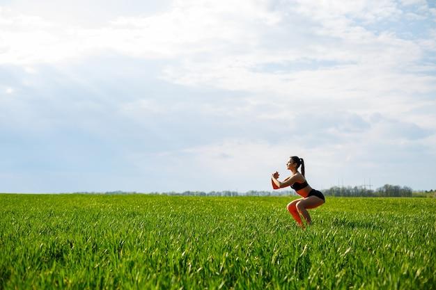 A menina atleta faz agachamentos na natureza, exercícios para as nádegas. jovem pratica esportes, estilo de vida saudável e corpo atlético. ela está em roupas esportivas, blusa preta e shorts.
