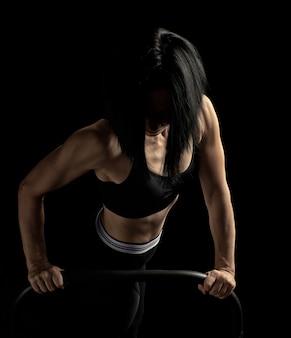 A menina atlética bonita nova com músculos em um sutiã preto é torcido em seus braços
