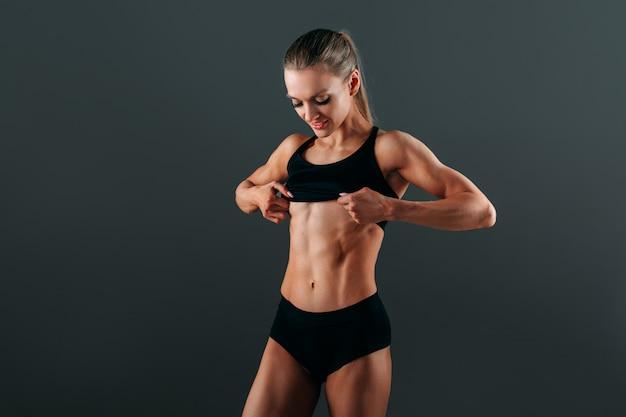 A menina atlética bonita nova com uma figura atlética bonita mostra seus músculos.