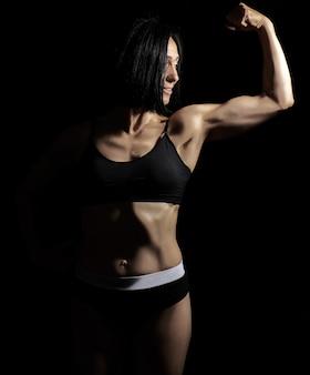 A menina atlética bonita nova levantou e dobrou o braço demonstrando seu bíceps