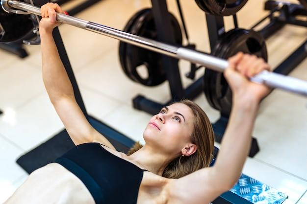 A menina atlética levanta o barbell que encontra-se no banco no simulador no gym.