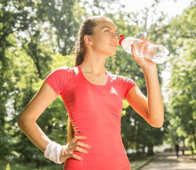 A menina atlética nova bebe a água após a corrida.