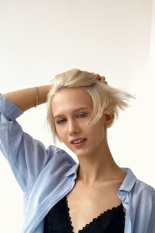 A menina atrativa à moda nova no equipamento ocasional toca em seu cabelo do voo.
