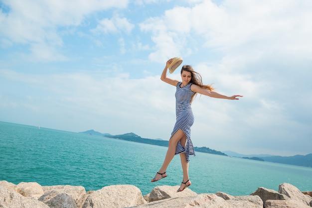 A menina atrativa no vestido salta em rochas na praia. lazer ativo, saúde, turismo, tema das férias.