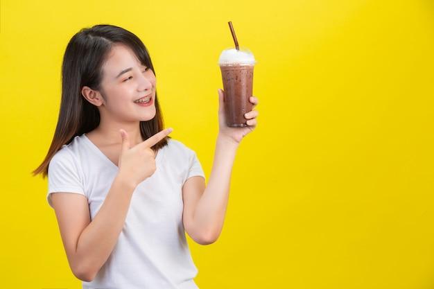 A menina bebe água fria de cacau de um copo de plástico transparente em um amarelo.