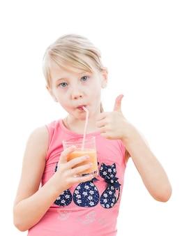A menina bebe batidos de laranja e levanta um dedo.