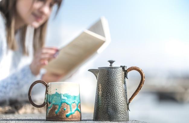 A menina bebe café e lê o livro ao ar livre