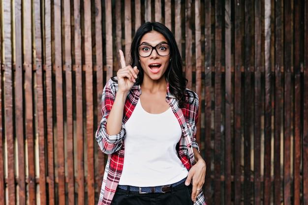 A menina bem humorada tem uma boa ideia. foto ao ar livre de emocional dama latina isolada na parede de madeira.