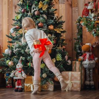 A menina bonita abre um presente de natal.