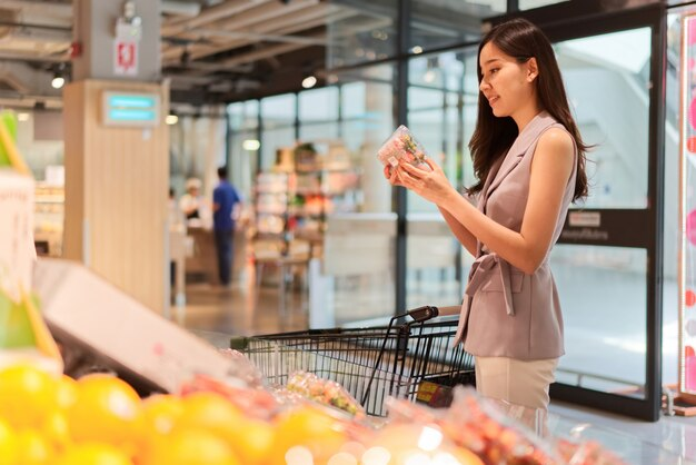 A menina bonita asiática nova está escolhendo frutas no supermercado.