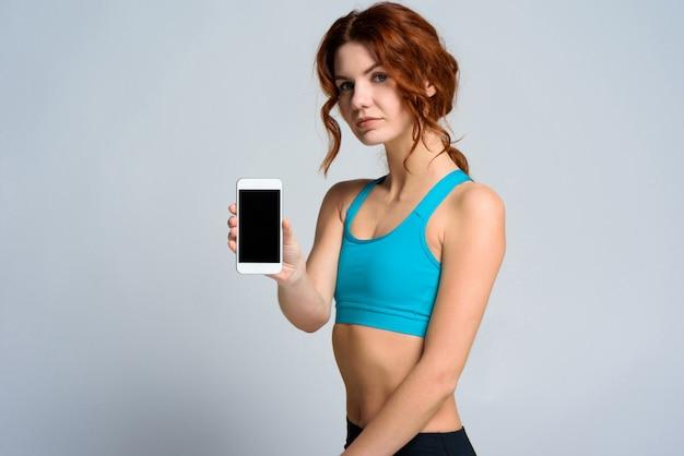 A menina bonita atlética apresenta um telefone novo.