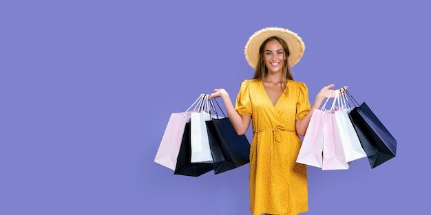 A menina bonita carrega roupas novas, enquanto segura pacotes coloridos com grandes promoções de cor de fundo