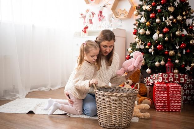 A menina bonita com a mãe sentada perto de árvore de natal em casa