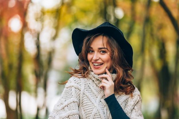 A menina bonita com cabelo encaracolado em um chapéu sorri na floresta no outono.