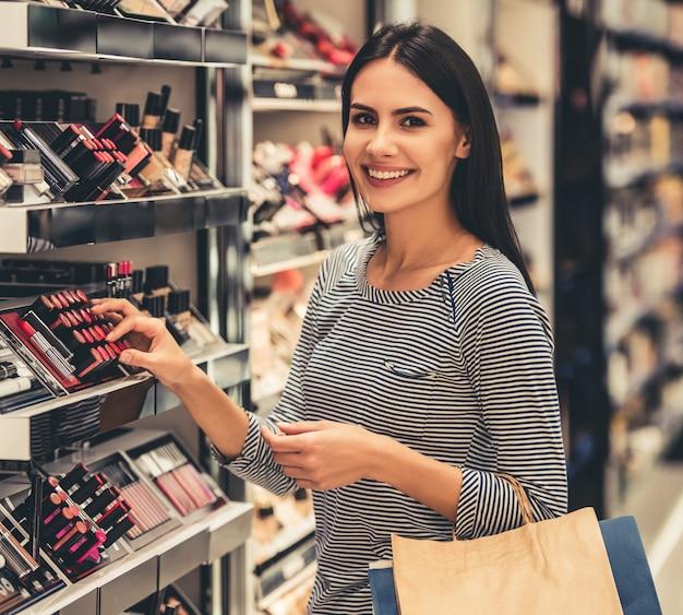 A menina bonita com sacos de compras está escolhendo o batom.