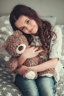 A menina bonita da escola está abraçando um urso de peluche.