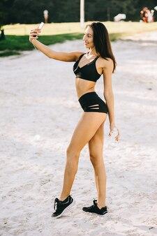 A menina bonita do cabelo escuro do lond no sportwear na praia faz o selfie