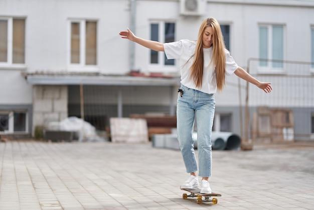 A menina bonita do estilo de vida do verão aprende montar um skate.
