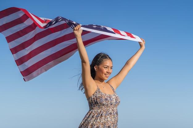 A menina bonita e feliz mantém uma bandeira dos estados unidos contra o céu.