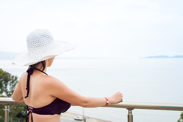 A menina bonita em um chapéu branco olha o mar e as montanhas em um dia ensolarado. férias de verão