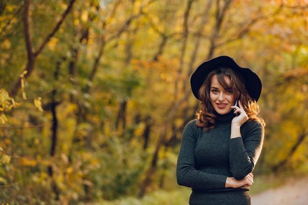 A menina bonita em um chapéu negro guarda um telefone em sua mão no parque no outono.