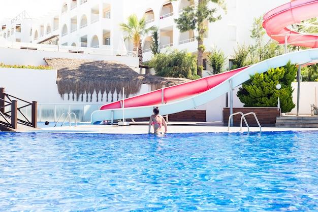 A menina bonita em um montante do roupa de banho sai da piscina. férias de verão