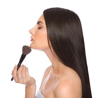 A menina bonita faz uma maquiagem olhando no espelho