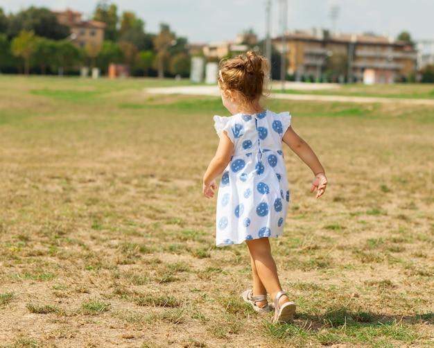A menina bonita joga ao ar livre em um dia de verão.