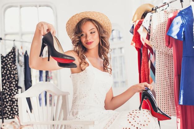 A menina bonita jovem escolhendo e experimentando sapatos modelo na loja