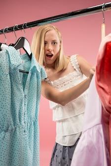 A menina bonita jovem olhando vestidos e experimentá-lo ao escolher na loja