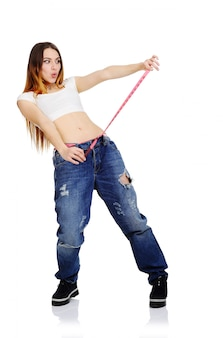 A menina bonita mede a cintura e aprecia uma figura magro em um fundo branco. perda de peso, perda de peso, dieta.