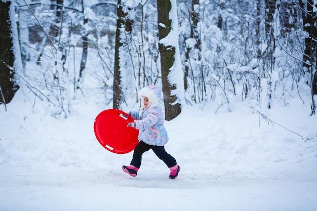 A menina bonita na roupa do inverno está no fundo nevado ao ar livre.