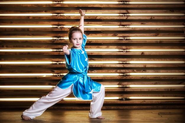 A menina bonita na sala em roupas esportivas para artes marciais é wushu ou kung fu
