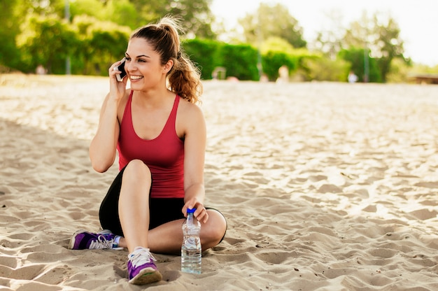 A menina bonita no esporte veste-se usando um smartphone e sorrindo ao descansar na praia após o exercício.