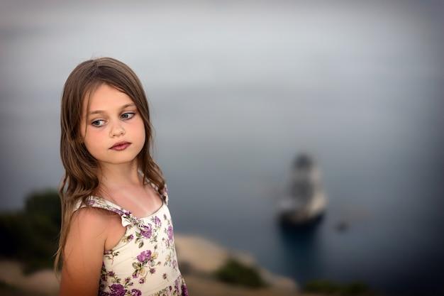 A menina bonita no vestido do verão com cabelo molhado está pensativamente pelo mar.