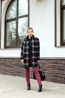 A menina bonita nova com um saco elegante está estando na rua