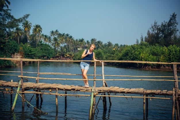 A menina bonita nova está na ponte de madeira sobre o rio pequeno contra a selva da palma e o céu azul.