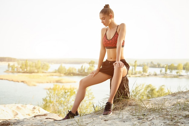 A menina bonita nova vestiu-se no sportswear e nas sapatilhas senta-se em um coto