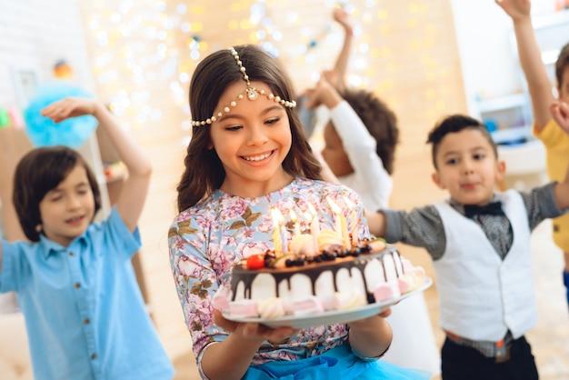 A menina bonita pequena guarda o bolo na celebração do aniversário.