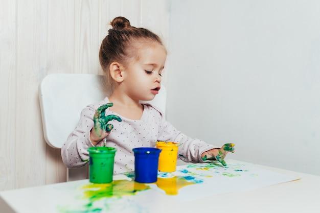 A menina bonita tira com pinturas do dedo em uma folha de papel branca.