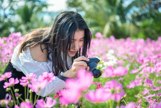 A menina bonita toma uma foto à flor do cosmos no jardim.