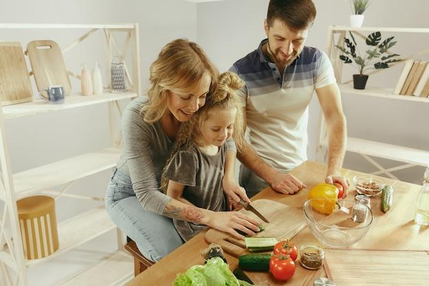 A menina bonitinha e seus lindos pais estão cortando vegetais e sorrindo enquanto fazem salada na cozinha de casa