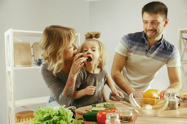 A menina bonitinha e seus lindos pais estão cortando vegetais e sorrindo enquanto fazem salada