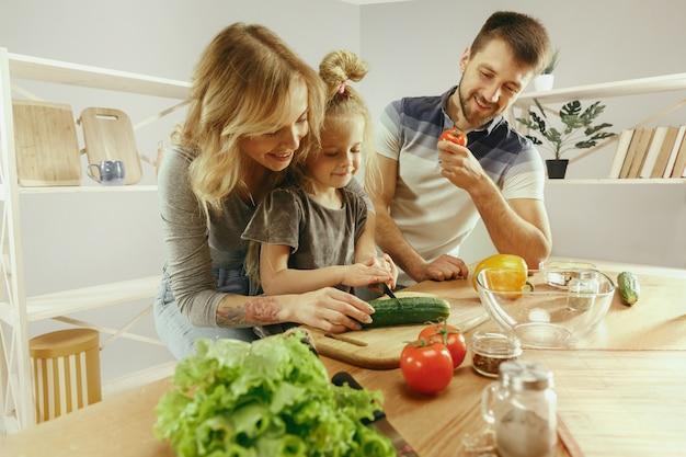 A menina bonitinha e seus lindos pais estão cortando vegetais e sorrindo