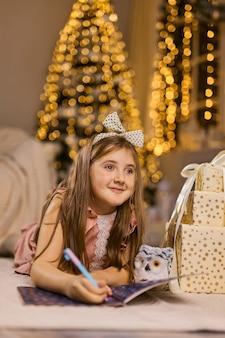 A menina bonitinha escreve a carta para o papai noel perto da árvore de natal dentro de casa