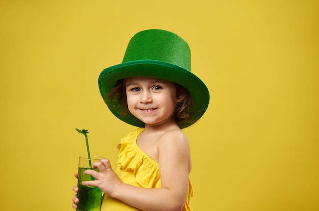 A menina bonitinha usa um chapéu verde irlandês de duende e sorri para a câmera com um copo de bebida verde nas mãos