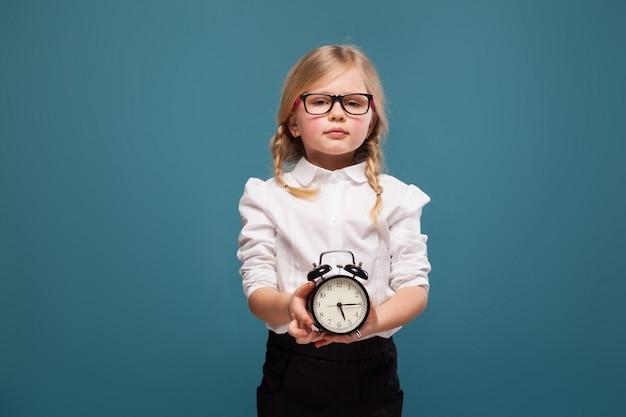 A menina bonito adorável na camisa branca, nos vidros e na calças preta guarda o despertador