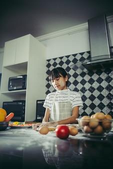 A menina bonito amassa a massa da farinha que prepara-se para faz a pizza. Conceito de cozinha.