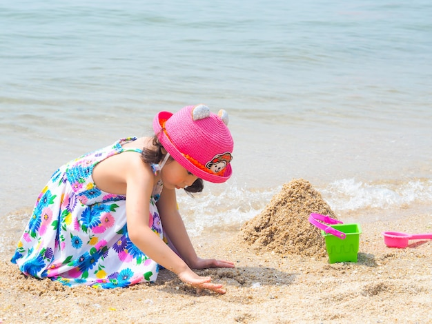 A menina bonito asiática que veste vestidos coloridos e o chapéu cor-de-rosa estão jogando a areia na praia.