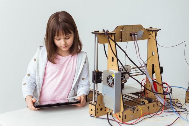 A menina bonito com máscaras impressas do obturador 3d está olhando sua impressora 3d enquanto imprime seu modelo 3d.